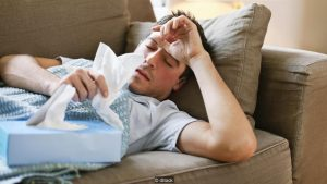 Man with a cold lying in sofa holding tissues